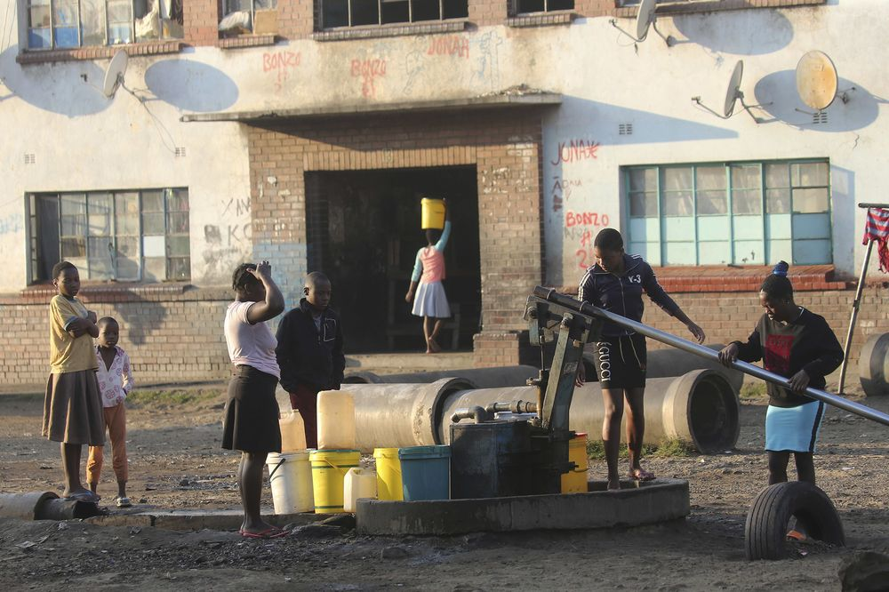 Children fetch water from a borehole in a poor neighborhood in Harare, Aug, 24.