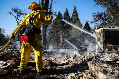 Firefighters work to contain embers on the remains of a destroyed house in Lower Lake, California on August 15.
