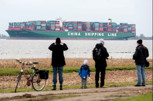 Strollers look at the containership stranded in the River Elbe
