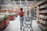 An employee completing an online customer order wheels a shopping cart through a Wal-Mart Stores Inc. outlet in Shenzhen, China.