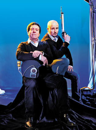 The founders with a motorcycle helmet-turned-automatic head-shaving device, and a harpoon used to play darts in their Underwater Nightclub video