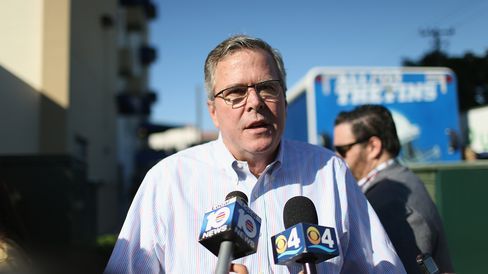 Former Florida Governor Jeb Bush speaks to the media as he hands out items for Holiday Food Baskets to those in need outside the Little Havana offices of CAMACOL, the Latin American Chamber of Commerce on December 17, 2014 in Miami, Florida.