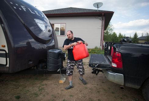 Evacuee A.J. Rosenthal carries a can of gas for his generator in Plamondon, Alberta.