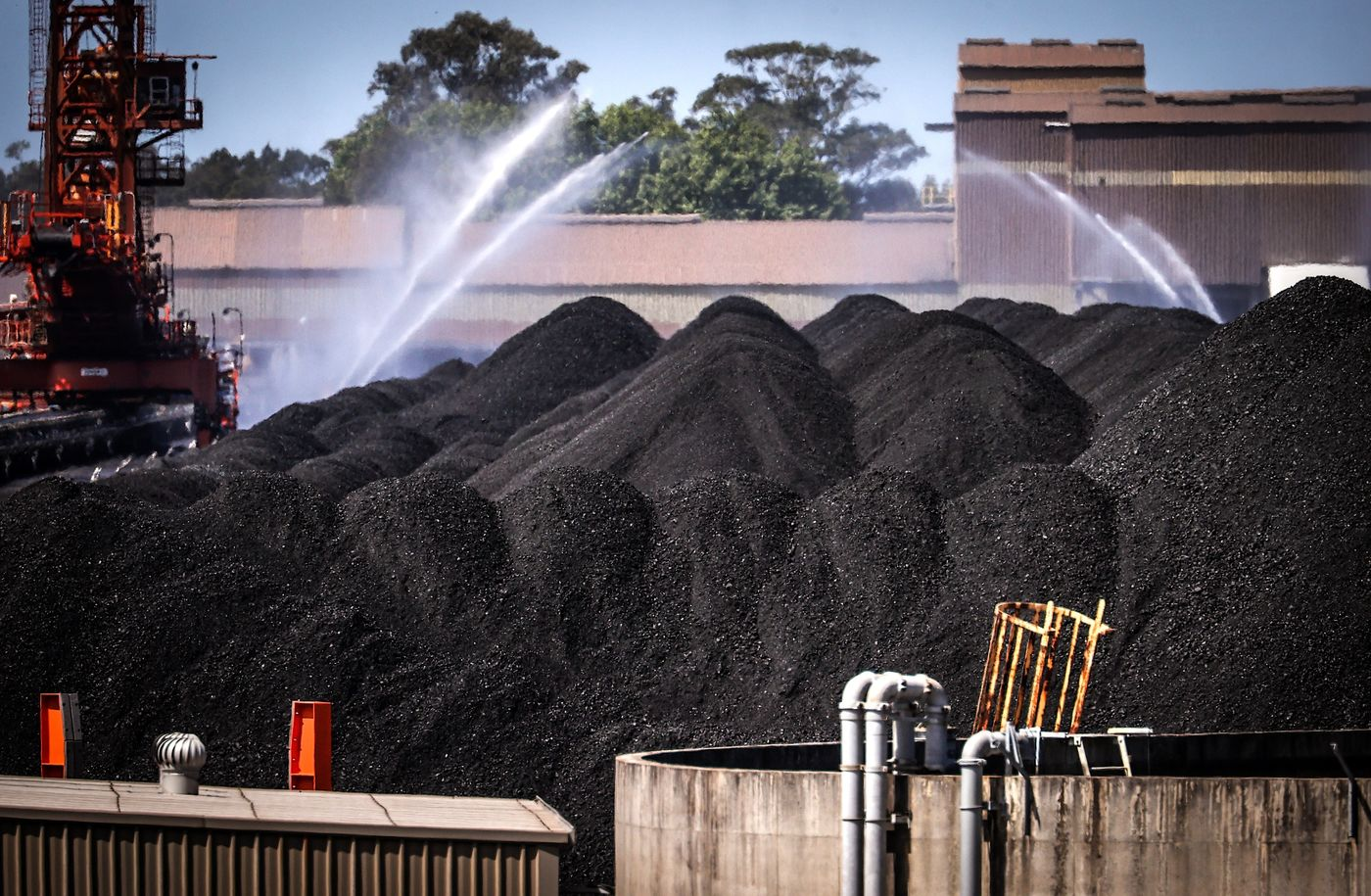 Water is sprayed over piles of coal at the Port of Newcastle in Australia on Oct. 12.