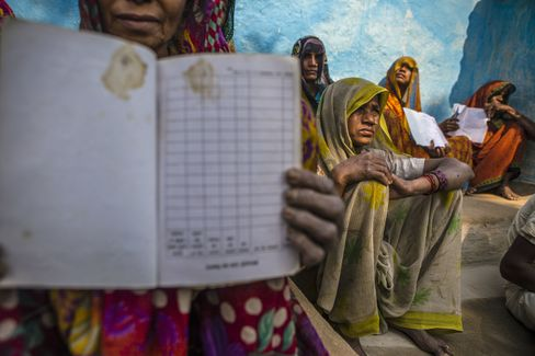 Villagers show their empty MNREGA job cards in the village square of Lar Sauryana.