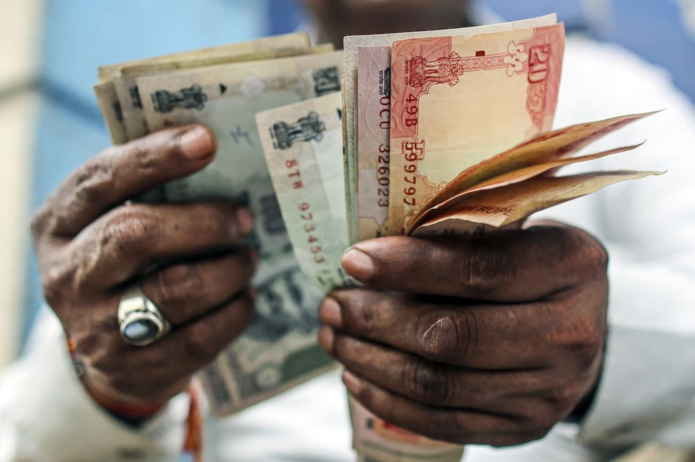 A Man Counts Indian Rubanknotes