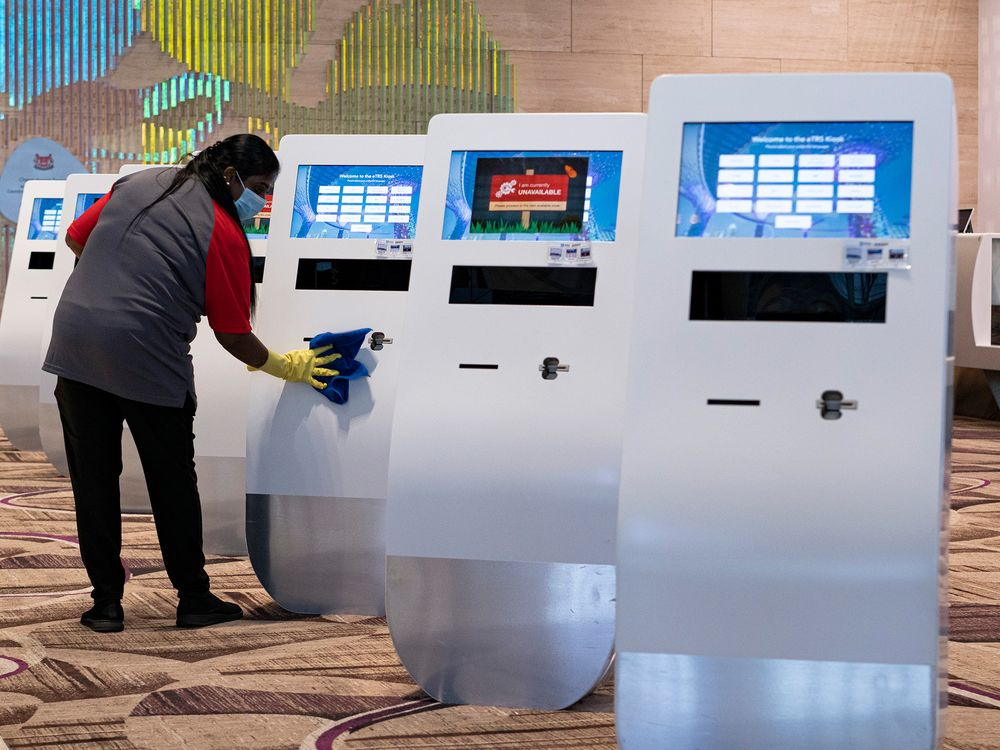 An employee wearing a face mask cleans a kiosk at the departure hall of Singapore Changi Airport.