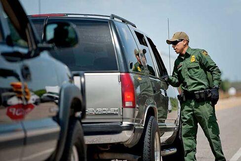 U.S. Border Patrol agent Jonan Lara checks vehicles for occupants identification at the Eagle Pass/Carrizo Springs interior checkpoint near Eagle Pass, Texas on July 3