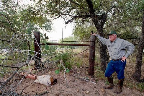 """Dr. Michael Vickers stands near a """"crawl hole"""" under the fence between his ranch and US Highway 281 south of Falfurrias, Texas on July 3"""