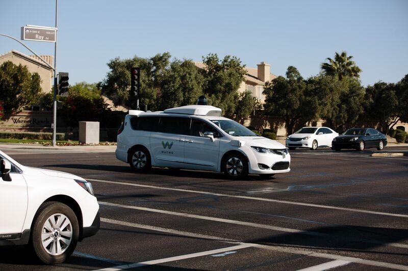A Waymo autonomous vehicle passes through an intersection in Chandler, Ariz.