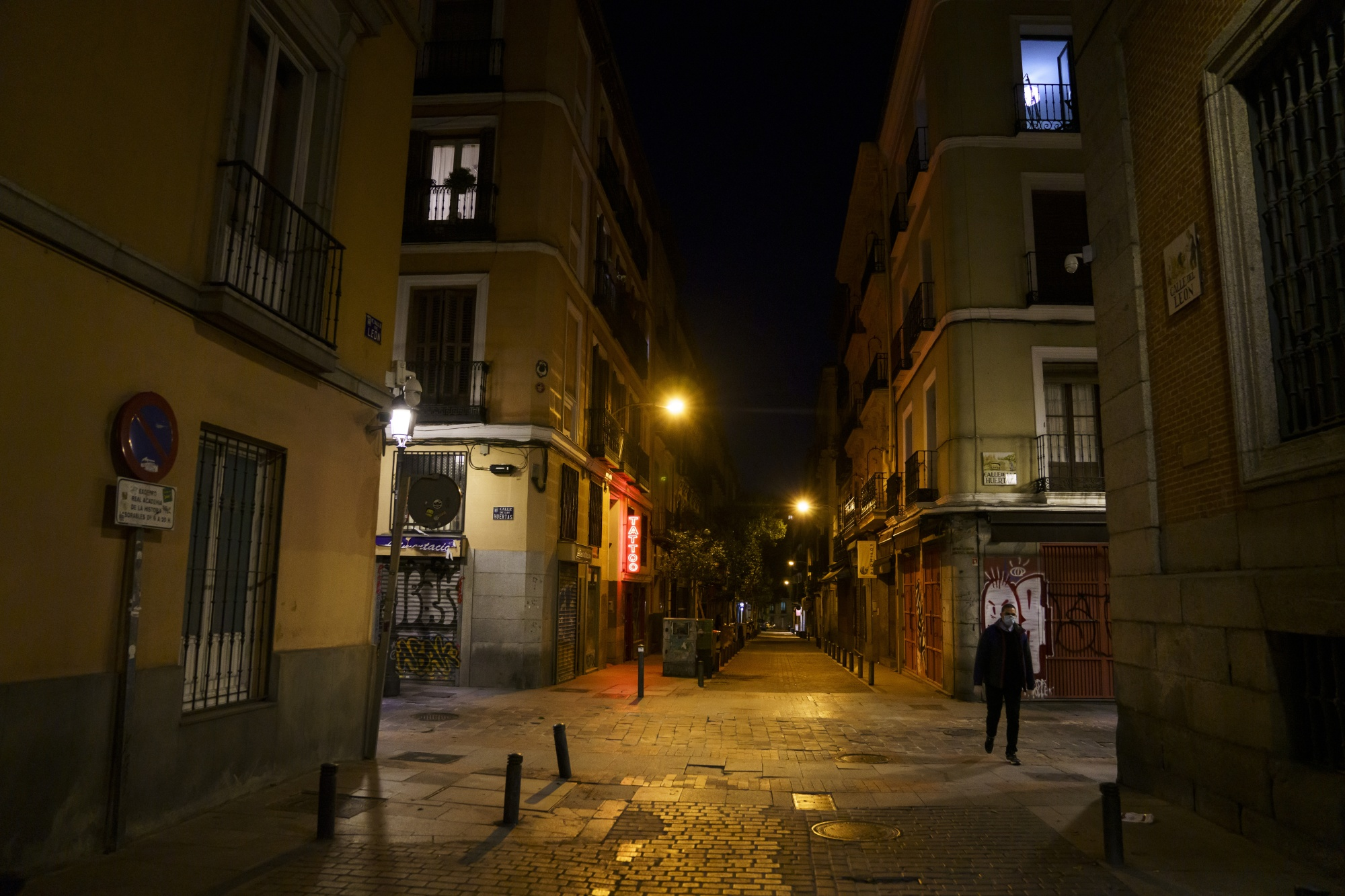 A pedestrian wearing a protective face masks walks by closed cafes and tapas bars at night in Madrid.