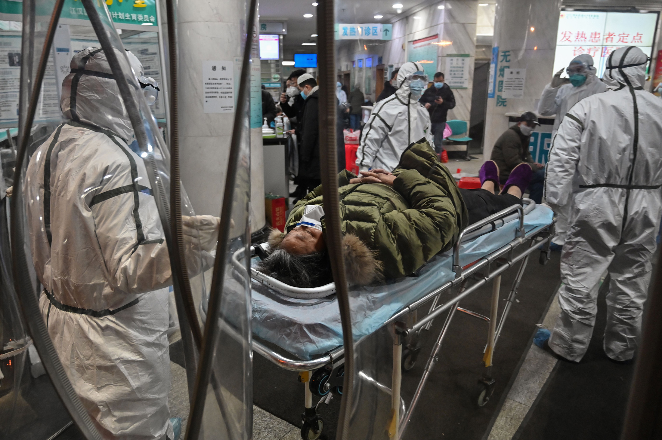 Medical staff members wearing protective clothing arrive with a patient at the Wuhan Red Cross Hospital in Wuhan on Jan. 25.