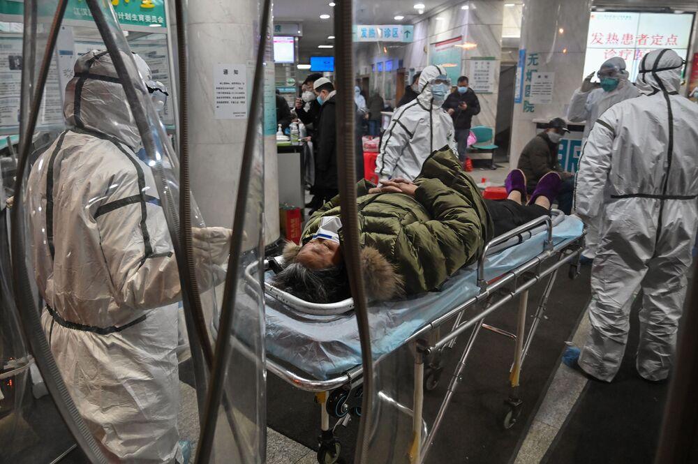 Nhân viên y tế mặc quần áo bảo hộ với bệnh nhân tại Bệnh viện Chữ thập đỏ Vũ Hán ở Vũ Hán vào ngày 25 tháng 1. Nhiếp ảnh gia: Hector Retamal / AFP qua Getty Images
