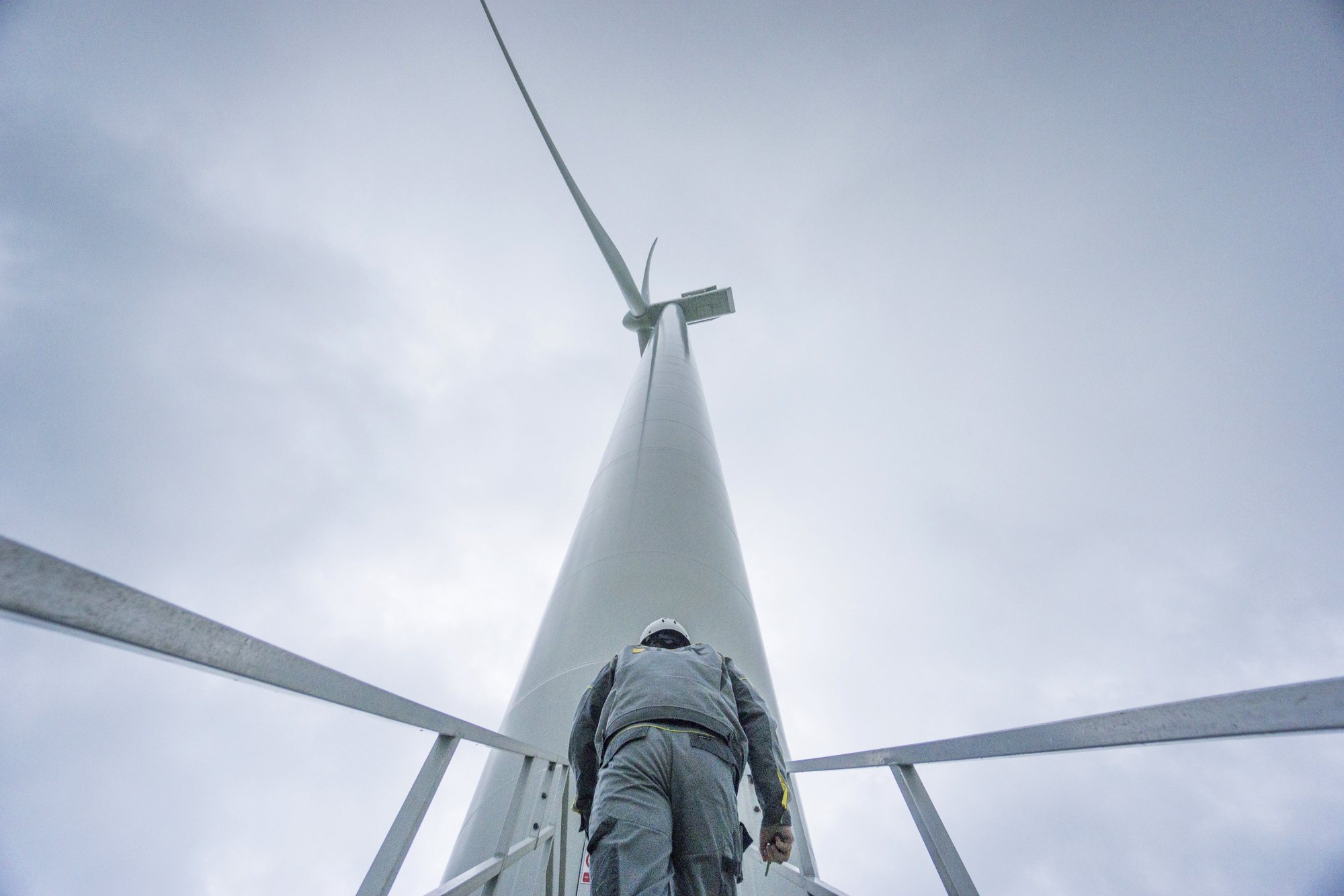 A worker climbs the access stairs to a Vestas Wind Systems A/S wind turbine at a windfarmin Botievo, Ukraine.