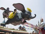 Visitors ride on the Dumbo The Flying Elephant ride at Tokyo Disneyland.