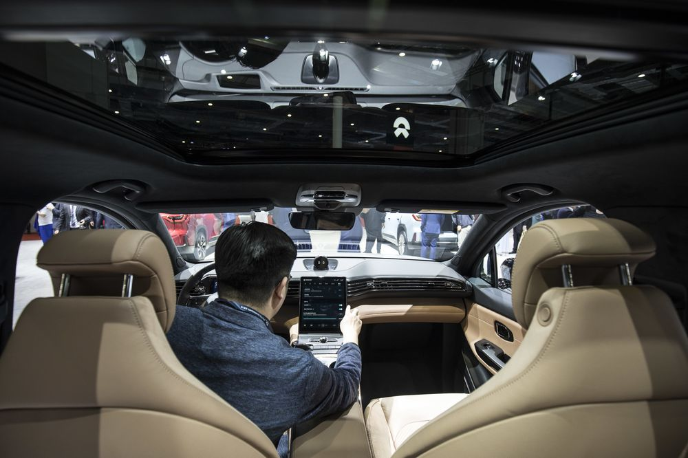 An attendee sits inside the NIO Inc. ES6 SUV on display at the Auto Shanghai 2019.