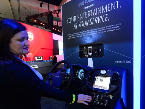 A Chrysler employee demonstrates functions on the U-Connect system display booth in Los Angeles, California.