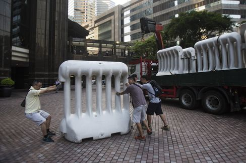 Workers move a barricade ahead of a visit by Zhang Dejiang on Monday. Photographer: Justin Chin/Bloomberg