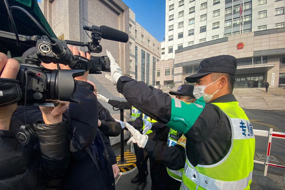 A policeman tries stop journalists from recording outside the Shanghai Pudong New District People's Court, where Chinese citizen journalist Zhang Zhanis set for trial on Dec. 28.