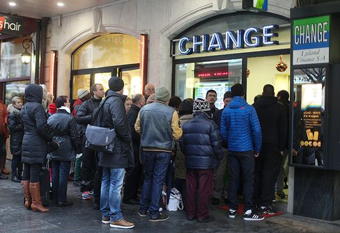 Customers wait in line to exchange currency at a bureau de change currency store, after the Swiss central bank ended the cap on the franc in Geneva, Switzerland, on Jan. 16, 2015.