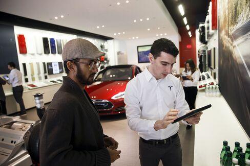 モデル3の先行予約で顧客に説明する従業員