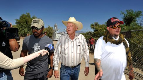 Rancher Cliven Bundy (center) with body guards departs after a news conference near his ranch on April 24, 2014, in Bunkerville, Nevada.