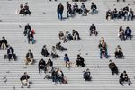 People rest and eat lunch on a bank of steps in La Defense business district of Paris, France.