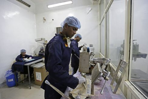 Workers process cow urine into capsules at Jains factory.