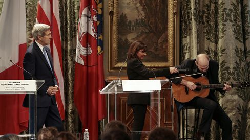Paris Mayor Anne Hidalgo (C) and US Secretary of State John Kerry (L) listen to US musician James Taylor at Paris City Hall on January 16, 2015. Kerry clasped French President Francois Hollande in a warm embrace during his visit in Paris on January 16 and said the US shared France's pain after its deadliest attack in half a century.