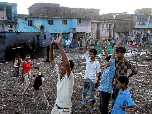 Children play cricket at a playground in the Dharavi slum area of Mumbai. Photographer: Prashanth Vishwanathan/Bloomberg
