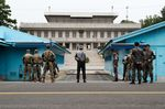 South Korean and U.S. soldiers stand guard next to United Nations Command Military Armistice Commission (UNCMAC) conference buildings .