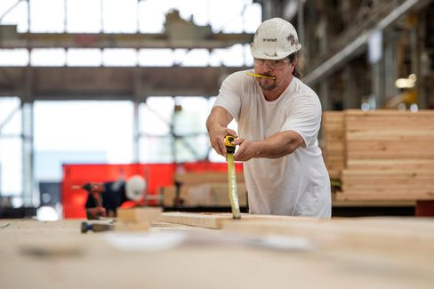 A worker uses a tape measure while assembling a floor at a modular home production facility in Vallejo, Calif. on Sept. 11.