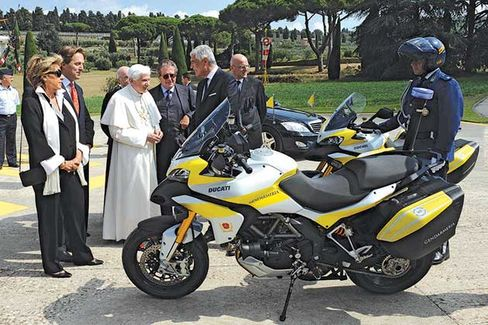 Bonomi (second from left) looks on as Pope Benedict is presented with two Ducatis in 2010