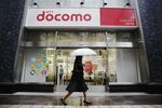 A woman holding an umbrella walks past an NTT Docomo Inc. store in Tokyo, Japan, on Friday, Oct. 28, 2016.