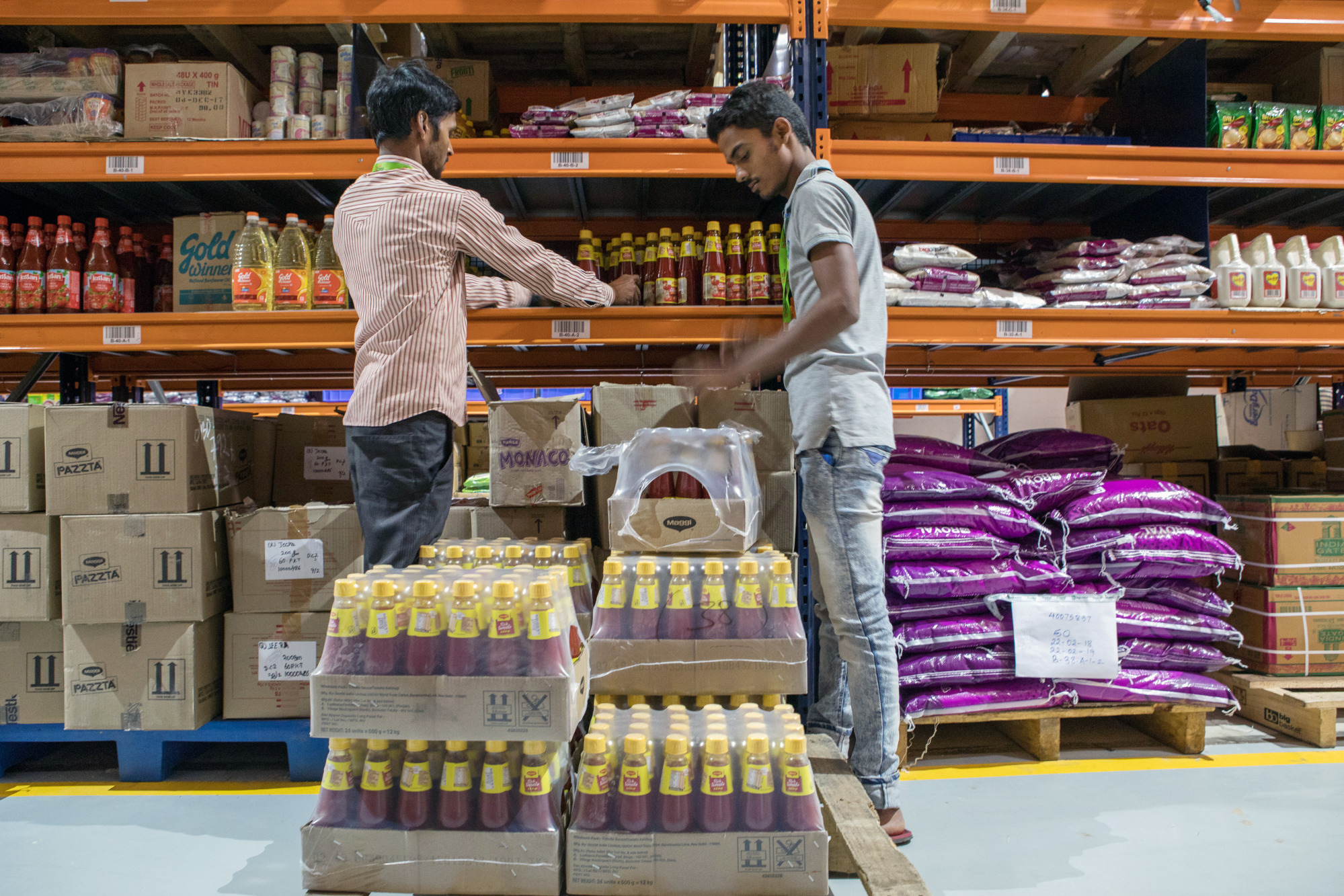 Workers unload crates of sauce at a BigBasket warehouse in Bengaluru, India, in 2018.