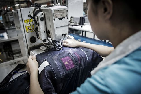 Workers prepare and make suits at a factory operated by the Shandong Ruyi Group.