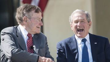 Former US President George H. W. Bush shakes hands with his son, former US President George W. Bush's, during a dedication ceremony at the George W. Bush Library and Museum on the grounds of Southern Methodist University on April 25, 2013 in Dallas, Texas.