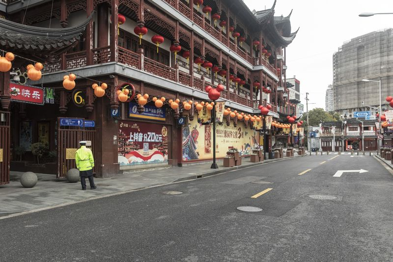 A security guard stands outside the empty Yuyuan Bazaar in Shanghai, Feb. 7.