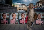 A woman walks next to election posters in StockholmSept.1.