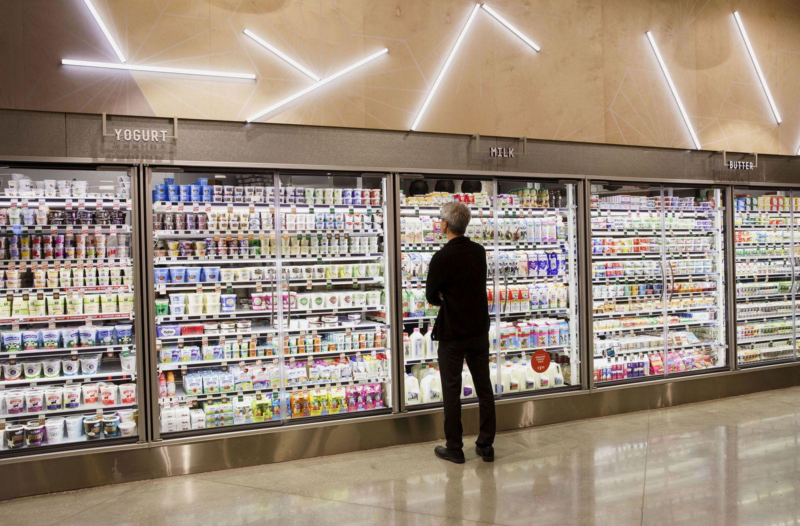 A customer browses the dairy section of grocery store in Los Angeles, Calif.