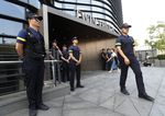 Police officers stand guard a building where the Japanese embassy is located in Seoul.