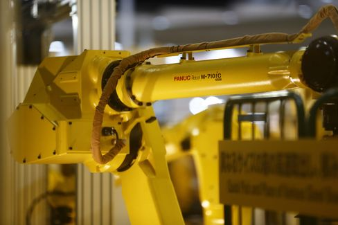 A Fanuc industrial robot lifts a vehicle during a demonstration