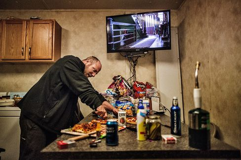 "East of Watford City, N.D., ""Bam"" sliced a microwave pizza he made for dinner at the Raven Drilling ""man camp"" near to their drill site, on July, 26, 2014."