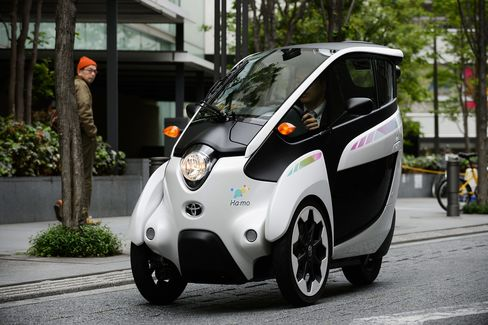 A Park24 employee drives a Toyota i-Road electric personal mobility vehicle along a street in Tokyo.