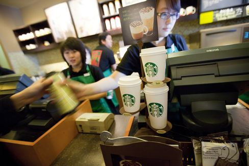 Servers help customers at a Starbucks Corp. store in Beijing