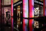 A man holding an umbrella walks past a Louis Vuitton store, operated by LVMH Moet Hennessy Louis Vuitton SA, in Shanghai, China.