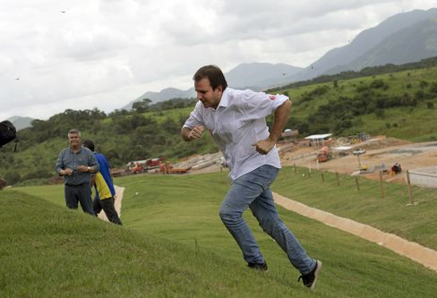Rio's Mayor Eduardo Paes runs up a hill to speak to journalists at Deodoro Olympic Park in April.