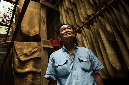 Farmer Winai Chaikunanant stands next to rubber sheets in a drying room