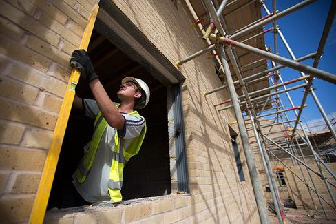A builder works in a window aperture during house construction at Persimmon Plc's St. Andrew's Park residential housing development in the Uxbridge district of London, U.K.