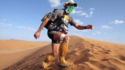 A competitor climbs a dune, during the t